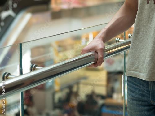 Tela Man holding a hand rail in mall staircase closeup