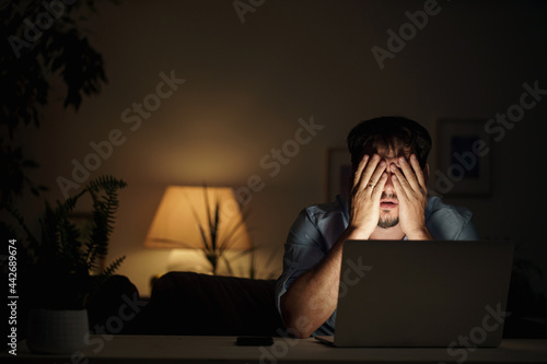 Fototapeta tired male businessman works at home at night on a laptop, works from a home office, studies online,