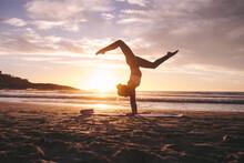 Woman Doing Yoga Pose Handstand On Beach