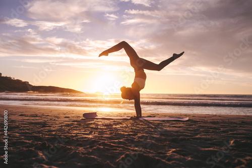 Woman doing yoga pose handstand on beach Fototapet