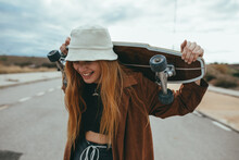 Joyful Young Woman Laughing While Standing On Road With Skateboard In Hands