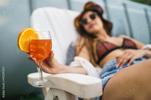 Orange fruit cocktail hold by a young woman sitting on a chaise lounge outdoors in the summer Fototapeta