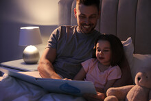 Father Reading Bedtime Story To His Daughter At Home