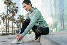 Positive Hispanic Sportswoman Tying Sneakers Before Running On City Square