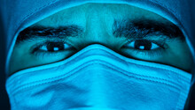 Male Doctor In Mask In Dark Room With Blue Neon Light