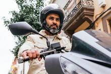 Hispanic Motorcyclist Driving Modern Bike On City Street
