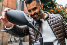 Crop Cheerful Hispanic Biker Looking In Side Mirror In Town