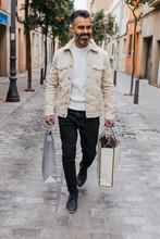 Smiling Hispanic Shopper With Gift Bags Walking On City Street