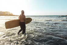 Surfer Senior Man Having Fun While Surfing On Beach With Vintage Surf Board - Focus On Head