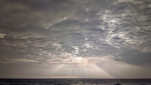 Crepuscular Sun Rays Streaming Through Overcast Monsoon Clouds Above The Sea