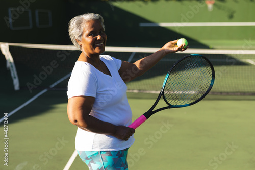 Portrait of smiling senior african american man holding tennis racket and ball on tennis court