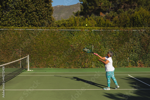 Senior african american woman playing tennis on tennis court
