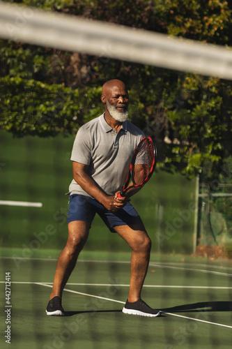 Senior african american man playing tennis on tennis court