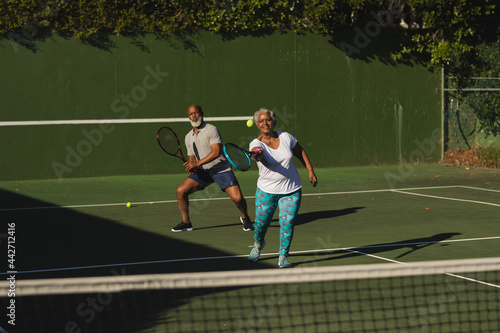 Senior african american couple playing tennis on tennis court