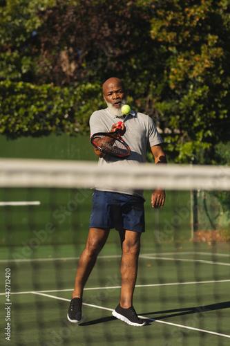 Senior african american man playing tennis striking ball on tennis court