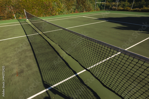 General view of tennis court and tennis net on sunny day