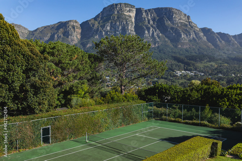 General view of tennis court in stunning countryside on sunny day