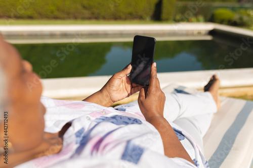 Senior african american woman using smartphone in deckchair by swimming pool in Fototapet