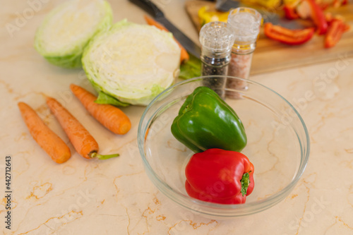 Close up of fresh vegetables lying on white countertop in kitchen