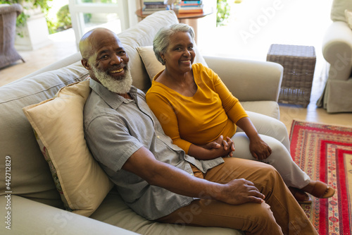 Portrait of senior african american couple sitting on sofa holding hands looking at camera smiling