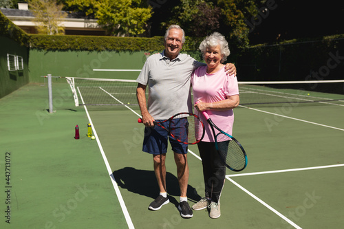Portrait of senior caucasian couple looking at camera and smiling on tennis court