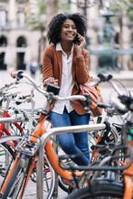 Cheerful Black Woman Talking On Smartphone Near Bicycle
