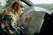 Driver Writing On Paper Map In Car During Trip