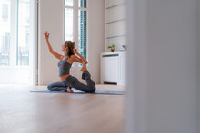 Slim Woman Practicing Yoga In King Pigeon Pose At Home