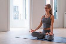 Calm Woman Doing Yoga And Meditating At Home