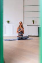 Woman Sitting In Lotus Pose On Mat At Home