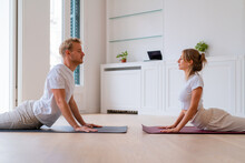 Couple Doing Yoga In Cobra Pose At Home