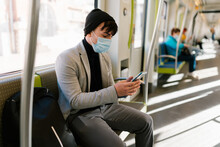 Man In Mask On Smartphone In Train