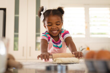 Happy African American Daughter Leaning On Kitchen Counter Rolling Dough With Rolling Pin