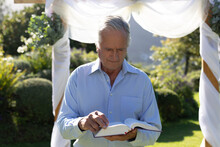 Senior Caucasian Male Wedding Officiant Preparing Before Wedding Ceremony