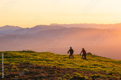 Fotografie, Obraz Mother and daughter cycling uphill with mountain bikes at a sunset