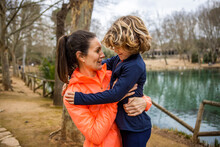 Son Embracing Mom Against Pond In Park