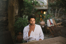 Young Dark Haired Boy Smoking A Cigar While Sitting On A Patio