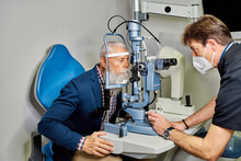 Ophthalmologist Using Slit Lamp For Eyesight Test In Clinic