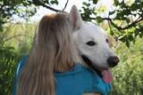 Fototapeta Kawa jest smaczna - Young woman hugging her white Swiss Shepherd dog in park, back view