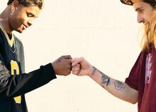 Crop Multiethnic Male Friends Bumping Fists In Sunlight
