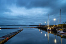 Harbor With Boats And Jetties At Night Under Cloudy Sky