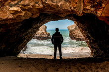 The Silhouette Of A Man In A Dark Cave With A View Of The Raging Ocean And Rocks
