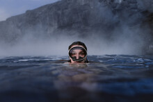 Woman With Goggles Diving Into The Sea Looking At Camera