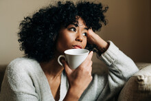 Thoughtful Black Woman With Cup Of Drink Looking Away