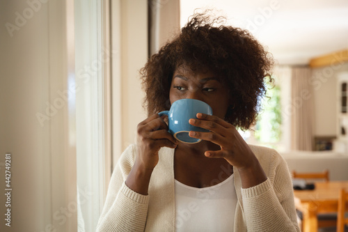 Thoughtful african american woman standing in dining room drinking cup of coffee
