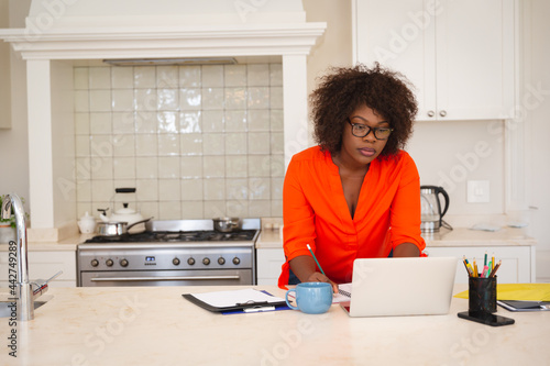 African american woman working in kitchen, leaning on counter, using laptop and writing notes