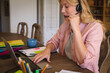 Caucasian woman working in dining room, wearing headset, using laptop and talking during video call