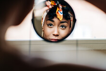 Charming Black Woman In Headband Looking In Round Mirror