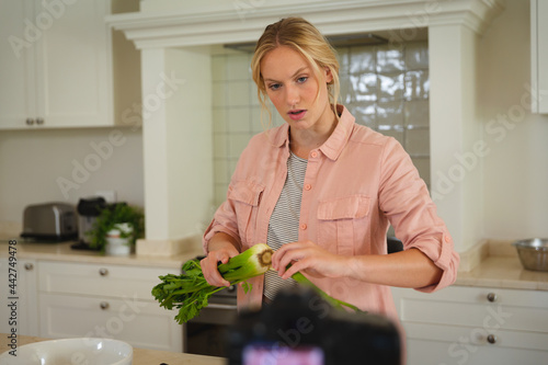 Caucasian woman in kitchen preparing food and using camera, making cooking vlog
