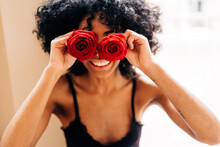 Delighted Black Woman With Rose Flowers